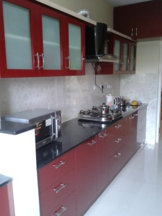 A parallel style kitchen done in berry tones with embossed tiles