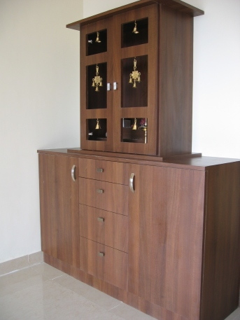 A Pooja unit with brass antiques combined with a storage unit