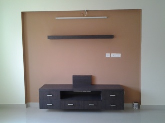 Mustard walls and contrasting brown display unit, with a custom made shelf