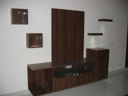 A media unit done in dark wood with displays to match